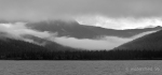 morning view across cold mountain lake to misted valley