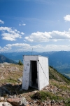 an out-house on top of a mountain, secured by steel cables and adorned with a lightning rod